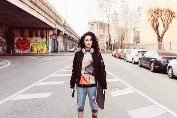 young woman skater posing city