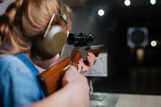 Nice pleasant girl developing her shooting skills