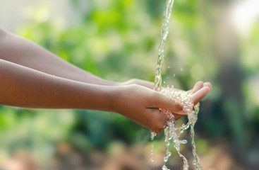 Water pouring in kid two hand on nature background