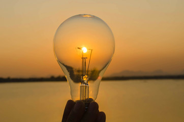 concept hand hold lightbulb and sunset background nature idea