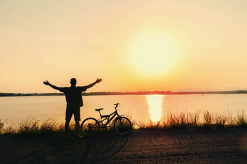 silhouette human freedom of cyclist in nature background and beautiful sunset