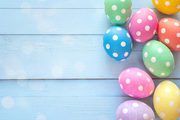 Colored Easter eggs on blue wooden background. Space for text.