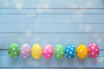 Colored Easter eggs on blue wooden background.