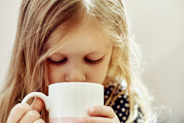 Close-up portrait of cute little girl drinking hot tea indoors.