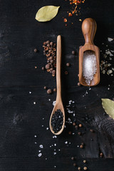 Black himalayan and white sea and fleur de sel salt in wooden spoons with black, chili, allspice pepper and bay leaves over black burnt wood background. Top view with space