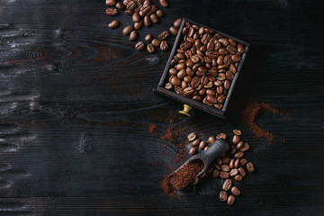 Roasted coffee beans and grind coffee in wood box with scoop over black wooden burnt background. Top view with space.