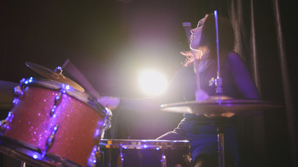 Attractive young girl rock musician - female drummer performing