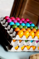 Stacked molded pulp egg carton with colorful bright rainbow painted easter eggs. Selected focus.