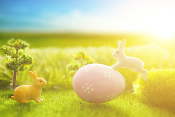 Little Easter bunny and Easter eggs on green grass over sunset. Macro.
