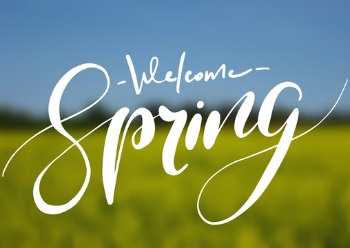 Welcome spring handwriting lettering design on blurry blossom field landscape.