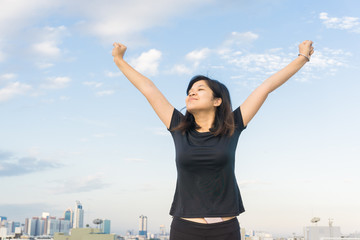 Women stretch body on top of building for running