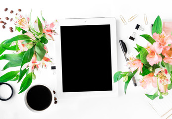 Workspace with tablet with blank screen, office accessories, coffee, flowers