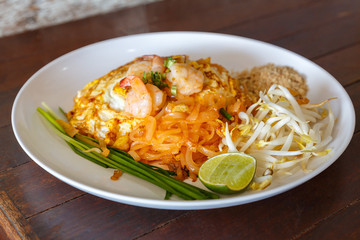 Fried noodle Thai style with prawns(Pad Thai) on wooden background
