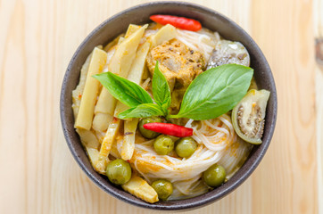 Rice noodles in chicken curry sauce with vegetables on wooden background