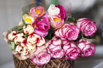 Pink roses and colored tulips are in the basket
