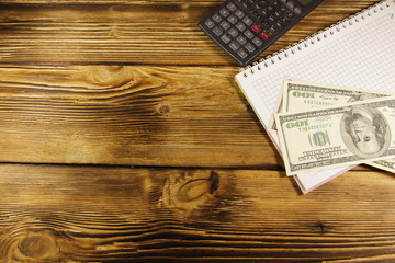 Notebook with dollars and calculator on wooden desk