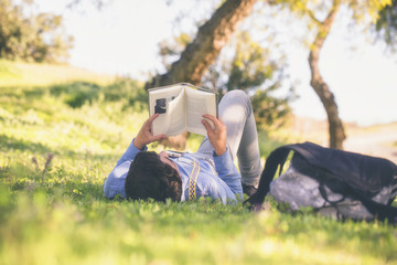 64/5000 Quizás quisiste decir: joven adolescente lee tumbado sobre la hierva en un día soleado Young teenager reads lying on the grass on a sunny day