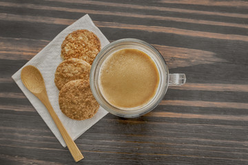 Coffee and cookies on a wooden table with a wooden spoon