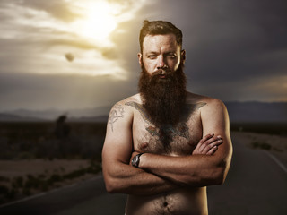 portrait of sexy bearded male hipster standing shirtless in nevada desert wearing only jeans and boxers