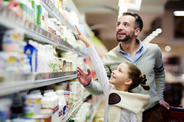 Happy girl pointing at pack of youghurt on upper shelf in supermarket