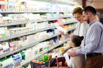 Modern family choosing dairy products in supermarket
