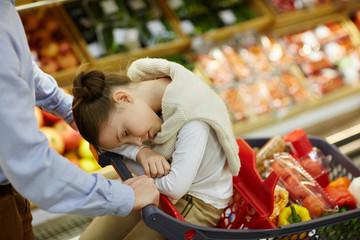 Cute girl sleeping in shopping-cart while her father pushing it