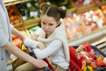 Gloomy girl sitting in shopping-cart being pushed by her mother in supermarket