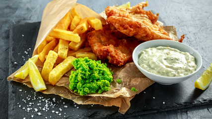 Photo Stands Ready meals British Traditional Fish and chips with mashed peas, tartar sauce on crumpled paper.