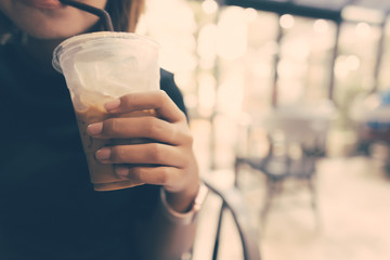 Asian woman drinking ice coffee in coffee shop in selective focus with vintage filter.