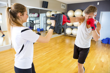 Boxer Punching Bag Held By Instructor In Gym