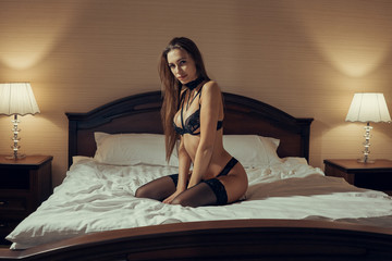 Seductive sexy gorgeous woman wearing lingerie in bed at home. Female underwear fashion.