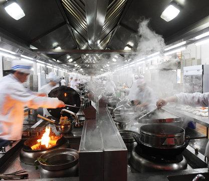 Motion chefs in a Chinese restaurant kitchen.