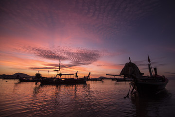 silhouette of many boat and man on sea of Thailand in sunrise