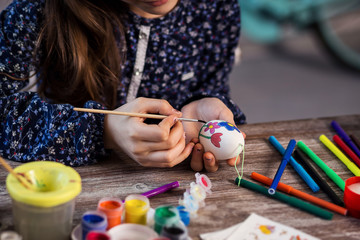 colouring eggs for eastertime at home.Happy easter!A mother and her daughter painting Easter eggs. Happy family preparing for Easter.decorating Easter eggs,children's hands hold a paintbrush and paint