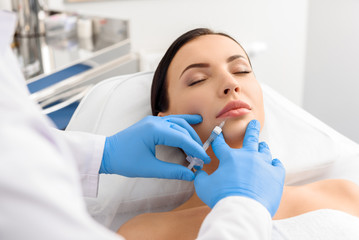 Woman tolerating anguish during cosmetic injection in lips