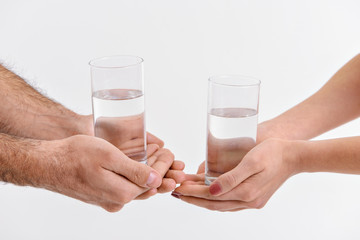 People keeping glasses with water