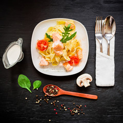 Restaurant food. Pasta with salmon on dark background. Flat lay, top view.