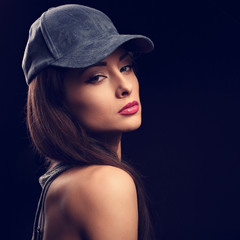 Beautiful sexy young make-up model profile in blue baseball cap with long hair style posing on dark black background. Closeup portrait