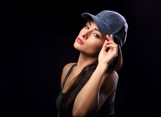 Beautiful sexy young make-up model profile in blue baseball cap with long hair style posing on dark black background with empty space