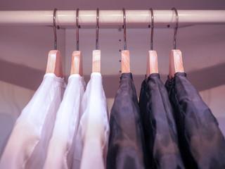 Row of men's suits hanging in closet.
