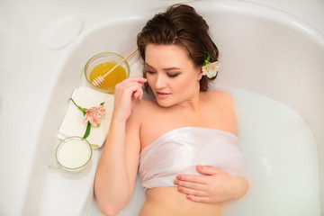 A young beautiful girl with brown hair lies in a bath with milk and honey in white clothes. Spa Relaxation