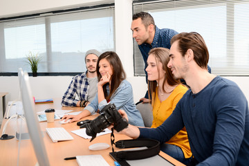 group of five young people student with their teacher in photography school learning photo editing with desktop computer, camera and photo equipment