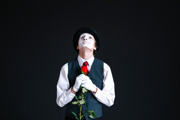 Mime looks up holding red rose before his heart