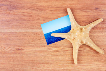 Top view of traveller's objects: photo card of the sea and sea star