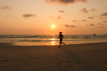 Women running on the beach at sunset time. silhouette of the girl exercise.