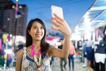 Woman taking selfie by mobile in night market at thailand