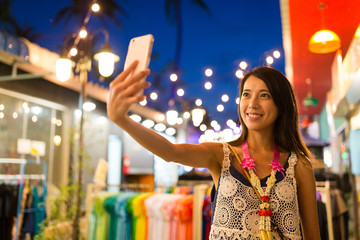 Woman taking selfie by cellphone at night in market
