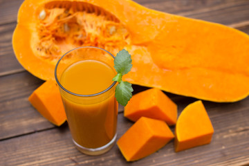 One portion of fresh pumpkin juice with mint leaf in a glasses on a rustic wooden background.