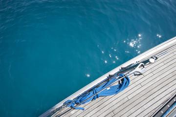 particolare zenitale del ponte in teak con cima d'ormeggio, di una barca in navigazione