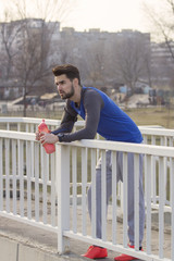 Jogger with bottle of water leaning on fence